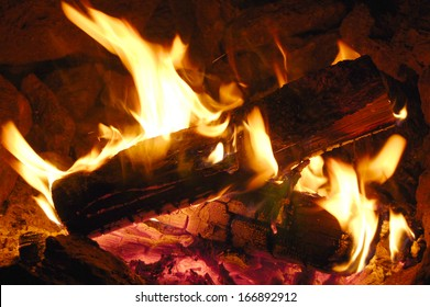 Campfire flames over burning logs