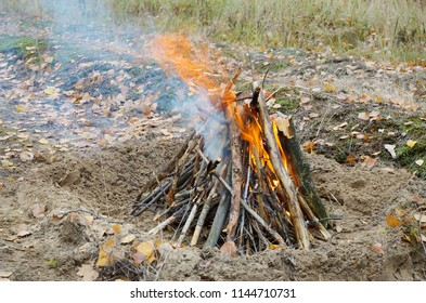 The campfire flares up. Red flame and bluish smoke over the fire. Dry firewood is vertically stacked in a small pit in sandy ground.