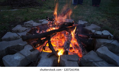 Campfire made in the place designed out of paving bricks set in the round pattern. Picture taken on the time of dusk.