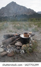 Campfire with morning coffee in stone fire ring with Rocky Mountain in the background