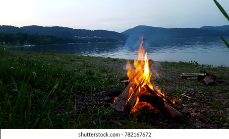 Campfire at night on the beach by the lake