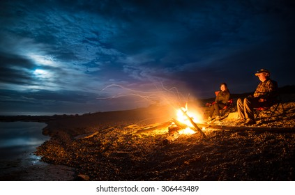 Campfire on a rocky beach with a couple sitting
