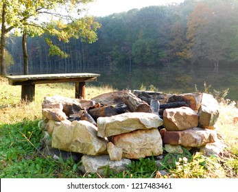 Campfire ring and bench in front of a pond taken in autumn in south central Pennsylvania, USA.  Image by AB at Pioneer Mountain Homestead.