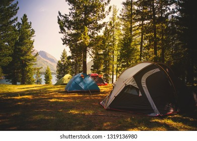 Campground in autumn taiga in Siberia. Tourists camped on the edge in the woods on a background of mountains and lakes. Adventure travel active lifestyle freedom outdoors.