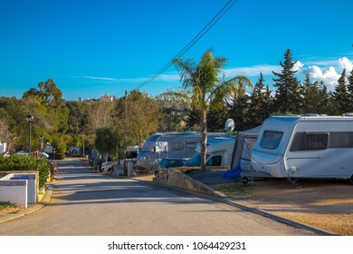Campground in south europe with RV and Caravans under a blue sky.