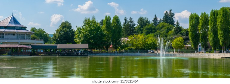 Campina, Romania - August 16, 2018: view of the cursed Bride's Lake or the Church Lake showing green trees and water fountain situated in Campina, Prahova, Romania.