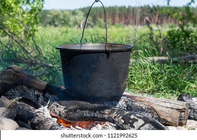 Camping, adventure, cooking a meal over an open flame campfire; Summer hike; Tourist kettle over the fire.