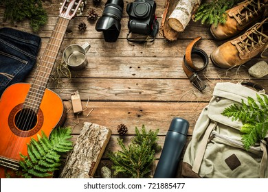 Camping or adventure trip scenery concept. Backpack, guitar, boots, belt, thermos and camera on wooden background captured from above (flat lay). Layout with free text (copy) space.