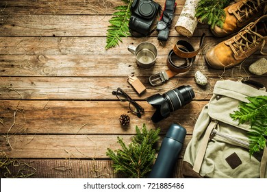 Camping or adventure trip scenery concept. Backpack, boots, belt, thermos and camera on wooden background captured from above (flat lay). Layout with free text (copy) space. Elements of nature around.