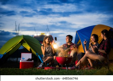 Camping of asian man and women group, relaxing, sing a song and cooking, with ligh from car and tent
