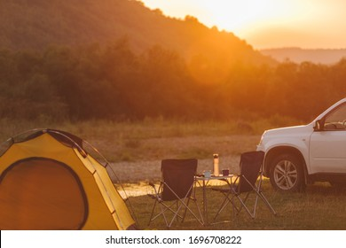 camping at beach of mountain river. suv car. yellow tent. camp table and chairs