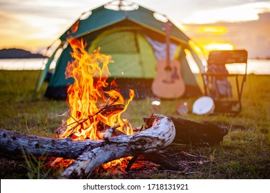 Camping bonfire surrounded by team of asian climbers hiker, they are playing music together in the forest path autumn season. Hiking, hiker, team, forest, camping , activity concept.