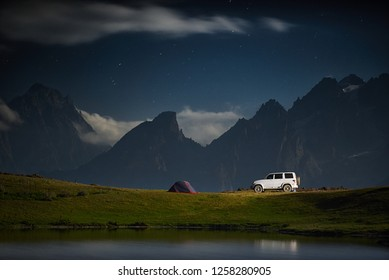 Camping with a car, tent at night with moonlight at mountain range