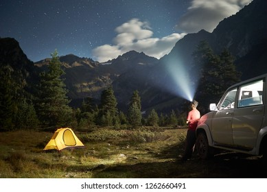 Camping with a car, yellow tent at moon night, man with headlight at mountains