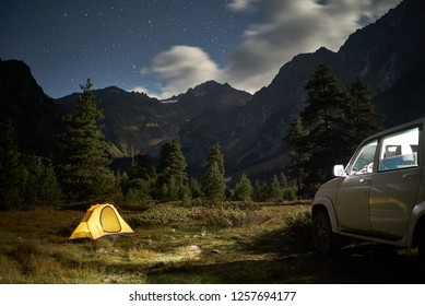 Camping with a car, yellow tent at night with moonlight at mountain area