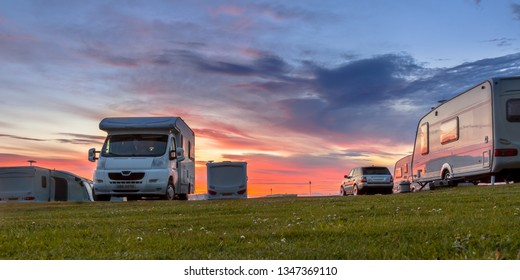 Camping caravans and cars parked on a grassy campground under beautiful sunset
