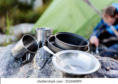 Camping cooking gear, pots and utensils in focus while an adventure man cooks food in the background next to an extreme weather tent outdoors in the mountains.