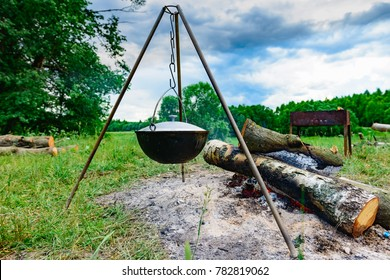 camping cook-kettle hanging on a tripod over a campfire on nature background of green grass