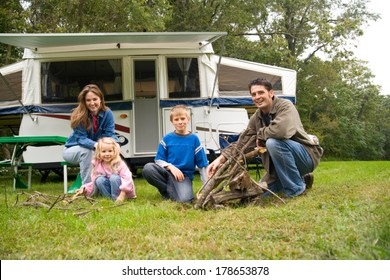 Camping: Cute Family Poses By Campfire Near Pop-Up Trailer