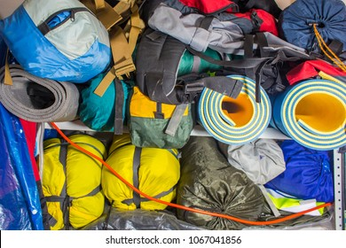 camping equipment for the hike - tents, backpacks, sleeping bags, messy stored on the shelf in the garage, waiting for new seasons