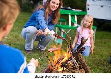 Camping: Family Cooking Hot Dog Over Campfire