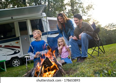 Camping: Family Having Marshmallow Fun By Campfire