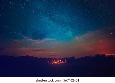 Camping fire under the amazing blue starry sky with a lot of shining stars and clouds. Travel recreational outdoor activity concept. - Shutterstock ID 567462481