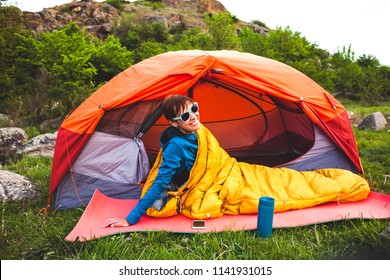 Camping in the forest. A girl is preparing coffee on a geyser coffee machine. A woman sits near a tent in a sleeping bag and prepares coffee against the background of the mountains.