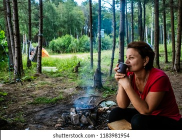 Camping in the forest. A woman is drinking tea by the fire