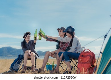 Camping group of friends asian people together, teenagers travel with backpack,tent clink beers bottle relaxing on vacation time holiday sitting on chairs near river and mountain view.