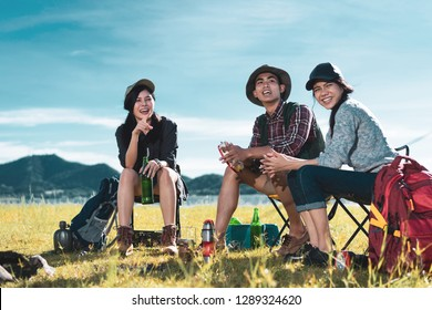 Camping group of friends asian people together, teenagers travel with backpack,tent man playing song relaxing on vacation time holiday sitting on chairs near river and mountain view.