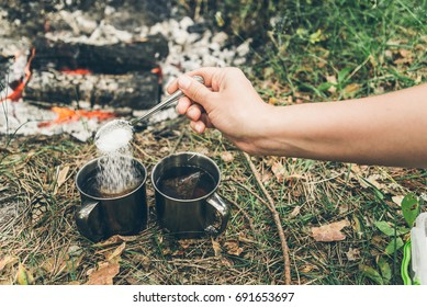 camping, hand put suger in metal cup near bonfire