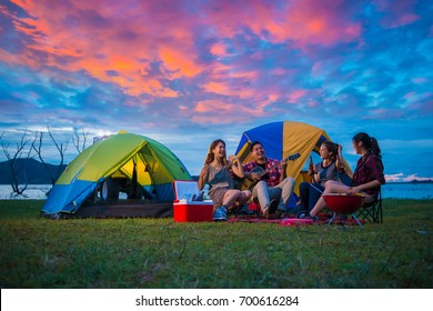 Camping of happy asian young travellers at lake, asian man and women group, relaxing, sing a song and cooking, at sunset.