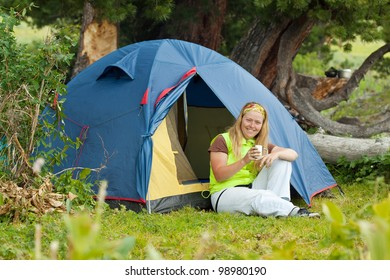 Camping happy woman drinking tea in front of tent