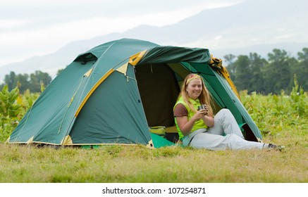 Camping happy woman front of tent against mountains