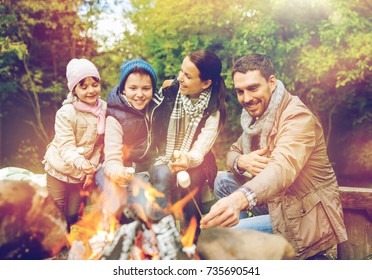 camping, hike and people concept - happy family roasting marshmallow over campfire