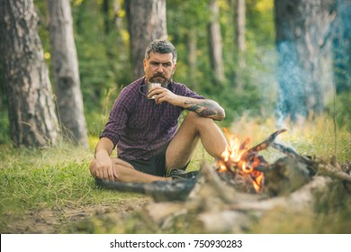 Camping, hiking, lifestyle. Hipster hiker with mug relax at bonfire in forest. Travel, traveling, wanderlust. Summer vacation concept. Man traveler drink tea at campfire flame.