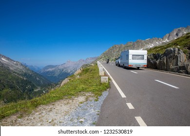 Camping holiday with the caravan. On the road to the beautiful family vacation. Camping Car in the Mountains. Road Trip with a Trailer. Summer vacation in the wilderness. Alpine region in Switzerland.