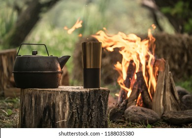 camping items by the fire kettle with thermos, travel concept and Hobbies