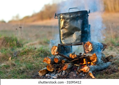 Camping kettle over burning  campfire in the morning light