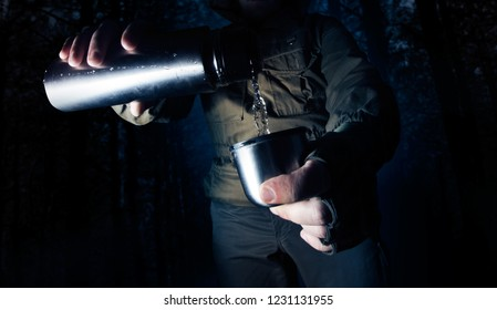Camping man in night forest pouring out water from thermos in a cup.