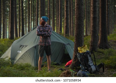 camping, man standing next to a backpack and a tent in  a birch forest