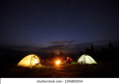 Camping in mountains at night. Bright bonfire burning between two tourists, boy and girl sitting opposite each other in front of tents under beautiful evening starry sky on distant hills background.
