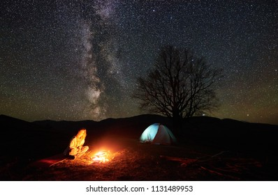 Camping night in mountains. Young female hiker having a rest near burning campfire under incredible starry sky and Milky way with glowing tent and silhouette of big tree in background