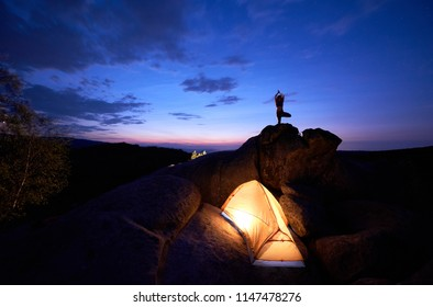 Camping at night on rock formation. Brightly lit tourist tent and small silhouette of woman doing yoga on mountain top against dramatic blue sky at sunset. Outdoor sport, yoga concept. Vrikshasana