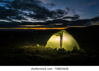 Camping in the nordic hemisphere with sunrise and a glowing tent