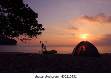 Camping on the beach with the shadow of the women in the tent and The men with daughter standing near the kayak at ang thong Island.