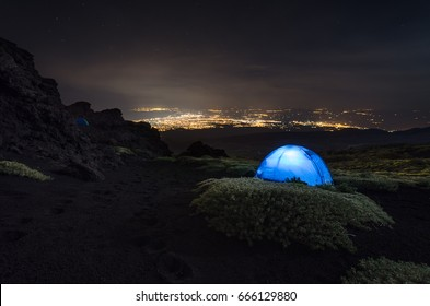 Camping on the mount Etna with the view of the city Catania.