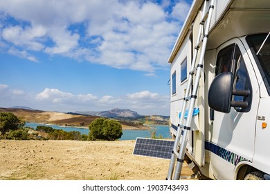 Camping on nature. Camper vehicle with portable ladder and solar panel. Caravanning equipment, maintain rv. Holiday trip with motor home.