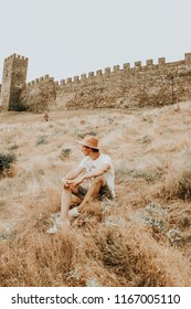 Camping outdoors and Mountains. Young man enjoying the view on the field against the background of the fortressin Europe. Film Vintage Modern colors. adventure at the weekend. Background for web